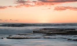 在岩石海岸的美好的剧烈的日落 库存图片