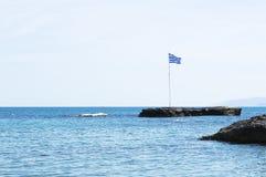 在岩石海岸线的希腊旗子 库存图片