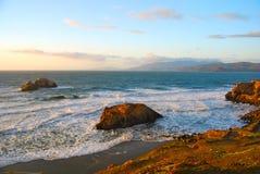 在岩石海岸线的日落在旧金山南部 免版税库存照片