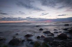 在岩石海岸线的日落,波罗的海 免版税图库摄影