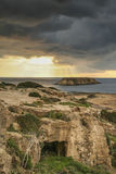 在岩石海岸附近的海岛在有风雨如磐的黑暗的天空的塞浦路斯 免版税库存照片