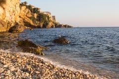 在岩石海海滩的日落 免版税库存照片