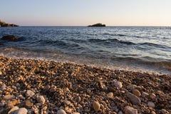 在岩石海海滩的日落 免版税图库摄影