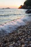 在岩石海海滩的日落 免版税库存图片