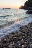在岩石海海滩的日落 库存图片