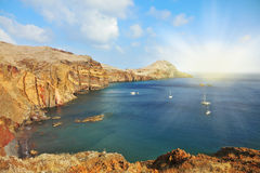 在岩石海湾的白色游艇 库存图片