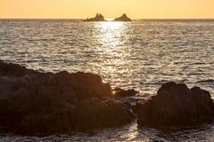 在岩石海滨的美好的日落 库存图片