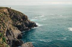 在岩石海边的独奏旅客,北部西班牙, B海湾  库存照片