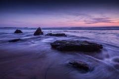 在岩石海洋海滩的紫色天空日落 免版税图库摄影
