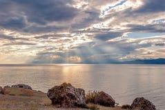 在岩石海滨的日落 免版税库存照片