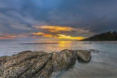 在岩石海滩的日落 免版税图库摄影