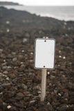 在岩石海滩的空白的标志 免版税库存照片