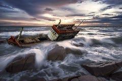 在岩石海滩的被击毁的小船被放弃的立场 免版税图库摄影