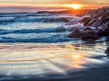 在岩石海洋跳船的日落 图库摄影