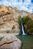 在岩石炎热的沙漠中的瀑布 免版税库存照片