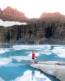 在岩石的一个女性身分在有高岩石和多雪的山的一个冻美丽的湖附近 免版税库存照片