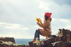 在岩石的上面的少妇享受日落看法在秋天森林生活方式和秋天概念的 免版税图库摄影