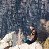 在岩石的上面的年轻人 免版税库存照片