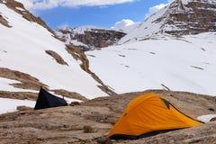 在岩石的两个野营的帐篷在雪山晚上 库存照片
