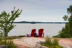 在岩石的两把红色椅子 免版税库存图片