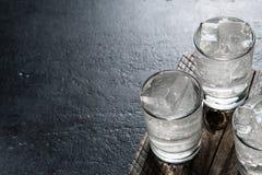 在岩石的伏特加酒在作为详细的特写镜头射击的一张老木桌上 库存照片