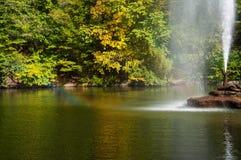 在岩石的喷水的喷泉在湖的中心 库存图片