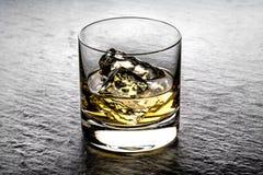 在岩石的威士忌酒在玻璃翻转者 免版税库存照片