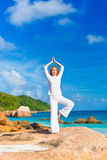 在岩石的少妇实践的瑜伽 免版税库存图片