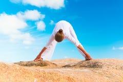 在岩石的少妇实践的瑜伽 库存图片