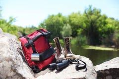 在岩石的旅行的齿轮在河附近 免版税库存照片