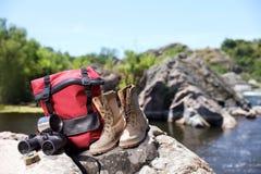 在岩石的旅行的齿轮在河附近 免版税库存图片