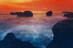 在岩石的日落在海洋上 库存图片