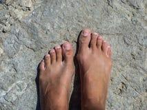 在岩石的桑迪脚 库存图片