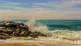在岩石的波浪在海滩 免版税库存照片