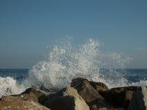 在岩石的波浪飞溅 库存照片