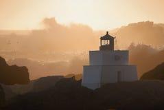 在岩石的灯塔与碰撞挥动在日落 免版税库存图片