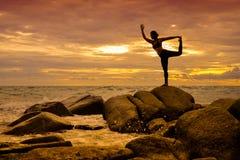 在岩石的瑜伽在与波浪私语的日落  库存图片