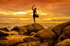 在岩石的瑜伽在日落 免版税库存照片