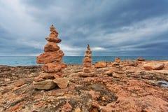 在岩石的石头堆靠岸在阴沉的天空下 免版税库存照片