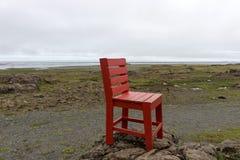 在岩石的红色木椅子 抽象横向 库存图片