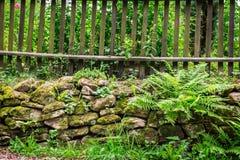 在岩石的老木篱芭 免版税图库摄影
