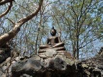 在岩石的菩萨雕象在森林里 免版税库存图片