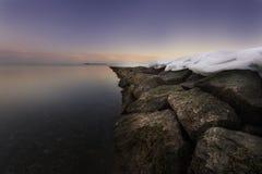 在岩石的雪在海滩紫色天空 免版税图库摄影