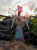 在岩石的高背包徒步旅行者举行扶手栏杆 在岩石的晴朗的破晓 有大背包、棒球帽、黑暗的裤子和白色衬衣的远足者 库存照片