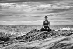 在岩石的黑白瑜伽在日落 免版税图库摄影