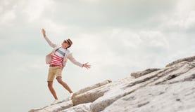 在岩石的年轻人跳舞,感受自由,蓝天背景 免版税库存照片