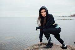 在岩石的年轻人适合的妇女在一种坚硬锻炼以后的立场和休息 免版税库存图片