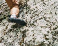 在岩石的登山人女性脚 免版税库存照片