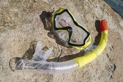 在岩石的黄色潜水面具 库存照片