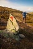在岩石的T有移动在挪威的背包的标志和远足者登上 库存图片